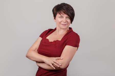 Closeup retrato de hermosa sonriente mujer de raza caucásica blanca de mediana edad morena con ojos azules en vestido rojo, mirando a cámara, sobre fondo claro en estudio