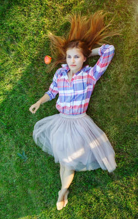 Portrait of young beautiful Caucasian woman with red messy hair lying with apple on grass in plaid shirt and tulle tutu skirt. View from above top overhead. Concept of spring summer youth happiness. Foto de archivo