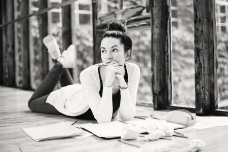 Black and white portrait of beautiful Caucasian young brunette woman student. Female artist lying on floor in college university drawing sketching. Person at work. Hobby activity concept Foto de archivo