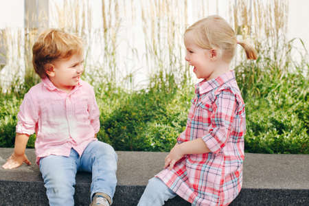 Group portrait of two white Caucasian cute adorable funny children toddlers sitting together talking smiling. Love friendship fun concept. Best friends forever.