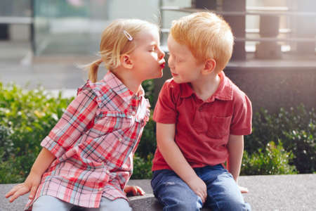 Group portrait of two white Caucasian cute adorable funny children toddlers sitting together kissing each other. Love friendship fun concept. Best friends forever. Foto de archivo