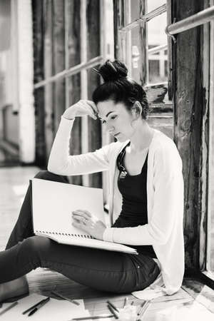 Black and white portrait of beautiful Caucasian young brunette woman student. Female artist sitting on floor in college university drawing sketching. Person at work. Hobby activity concept