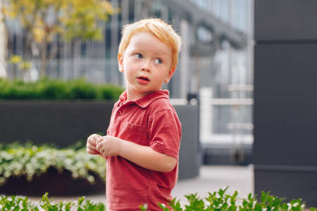 Closeup portrait of cute adorable little red-haired Caucasian boy child in red t-shirt standing in park outside looking away. Happy lifestyle childhood concept Foto de archivo
