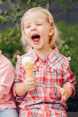 Portrait of cute white Caucasian blonde preschool girl with blue eyes in red pink shirt eating licking ice cream in waffle cone Reklamní fotografie