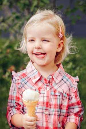 Portrait of cute white Caucasian blonde preschool girl with blue eyes in red pink shirt eating licking ice cream in waffle cone Foto de archivo