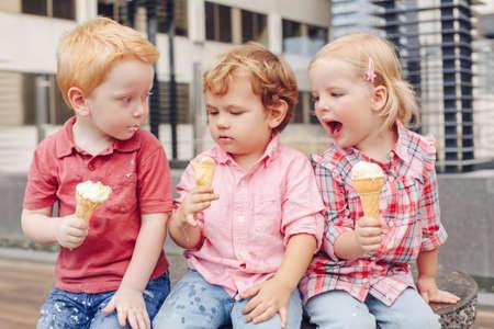 Groepsportret van drie witte Kaukasische schattige schattige grappige kinderen peuters zitten samen delen van ijs eten. Liefde vriendschap plezier concept. Beste vrienden voor altijd.