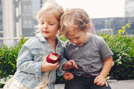 Group portrait of two white Caucasian cute adorable funny children toddlers sitting together sharing apple food. Love friendship childhood concept. Best friends forever