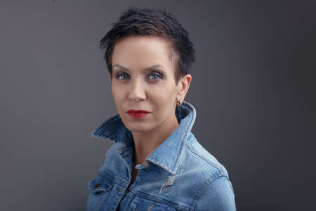 Studio portrait of beautiful cool edgy middle aged white caucasian brunette woman with blue eyes. Aged European sexy model with dark short hair looking in camera.