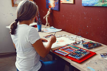 Portrait of Caucasian female artist painting flowers with watercolor paints and colored pencils. Woman painter at work in art studio. Lifestyle and hobby concept Foto de archivo