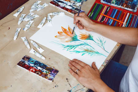 Hands of female artist painting flowers with watercolor paints and colored pencils in art studio. Lifestyle and hobby concept