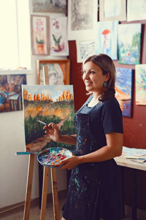 Portrait of young beautiful middle age white Caucasian woman artist drawing painting in art studio with acrylic paints on canvas. Lifestyle activity hobby concept