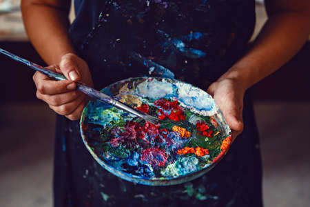 Hands of female artist holding messy dirty palette  with different paints and paintbrush in art studio. Lifestyle and hobby concept Foto de archivo