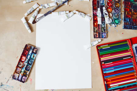 Watercolor paints, blank white paper and coloured pencils on table in art studio. Lifestyle and hobby concept. Mock up background with copyspace