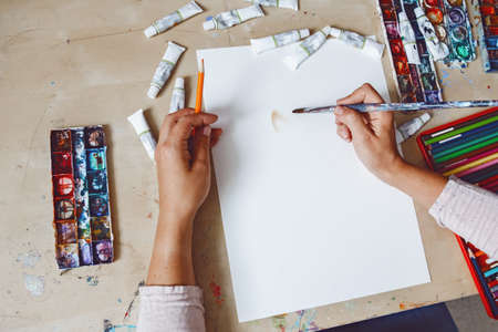 Hands of female artist painting with watercolor paints and colored pencils on white paper in art studio. Lifestyle and hobby concept