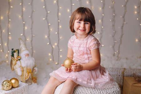 Portret van wit Kaukasisch kindmeisje met blauwe ogen die met speelgoed zitten die Kerstmis of Nieuwjaarsvakantie vieren