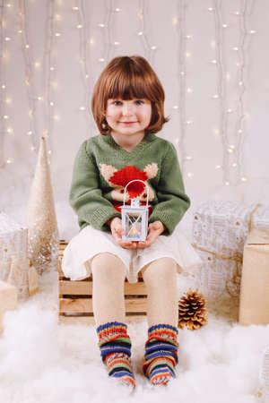 Portret van witte blanke kind meisje met blauwe ogen zitten met kaarslicht op zoek in de camera vieren Kerstmis of Nieuwjaar vakantie Stockfoto