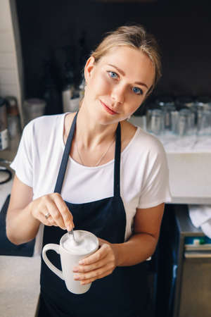 Portrait of young beautiful Caucasian woman barista stirring foam in cup of cappuccino coffee. Person at work, small business concept