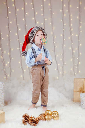 Portrait of white Caucasian boy wearing Santa Claus hat celebrating Christmas or New Year. Little adorable cute child eating licking candy lollipop in studio with winter holiday decoration
