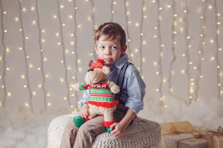 Portrait of sad upset white Caucasian boy holding deer moose toy celebrating Christmas or New Year. Little adorable cute child in studio with winter holiday decoration