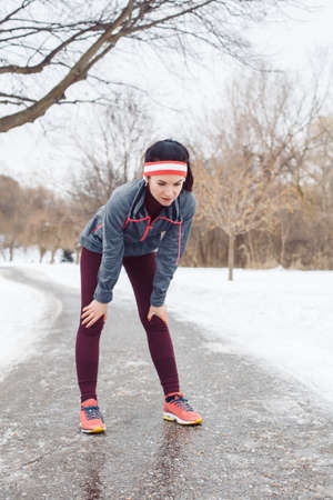Portrait of Caucasian young woman taking a break after  jogging outside in winter park. Girl resting after running outdoors wearing sportswear, headband and headphones. Banque d'images