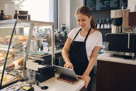 Portret van jonge Kaukasische vrouwelijke vrouwenkassier. Verkoper die touchpad gebruikt voor het accepteren van klantklantbetalingen. Kleine onderneming van coffeeshopcafetaria.