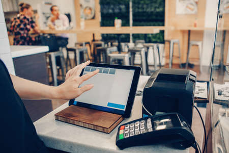 Closeup shot of caucasian cashier hands. Seller using touch pad for accepting client customer payment. Small business of coffee shop cafeteria. Banque d'images