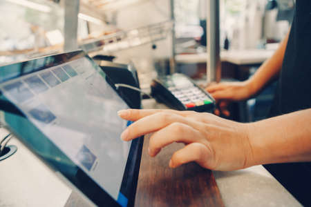 Closeup shot of caucasian cashier hands. Seller using touch pad for accepting client customer payment. Small business of coffee shop cafeteria. Archivio Fotografico