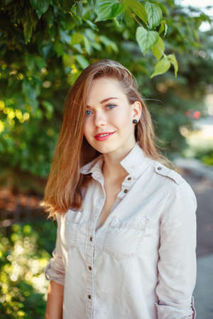 Portrait of beautiful smiling white Caucasian girl woman with long blonde hair and blue eyes wearing white shirt and jeans outside in summer park among green foliage trees looking in camera.