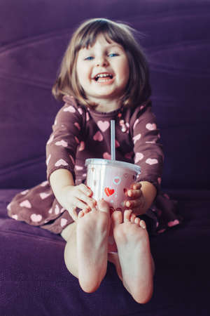 Portrait of cute adorable little girl wearing dress with hearts and crown sitting on couch. Child drinking from funny glass mug . Lifestyle happy childhood concept. Kid celebrating holiday Foto de archivo