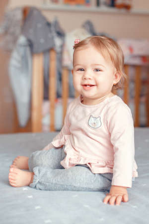 Portrait of cute adorable Caucasian blonde smiling baby girl with blue eyes in pink shirt sitting on bed in bedroom. Natural emotion face expression. Happy childhood lifestyle concept.