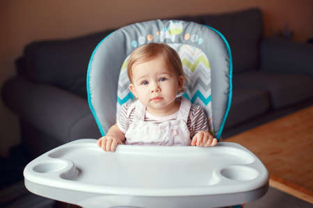 Portrait of cute adorable blonde Caucasian child girl sitting in high chair ready to eat. Everyday lifestyle. Candid real authentic moment. Kid one year old looking in camera Stock Photo