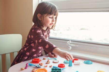 Portrait of cute white Caucasian preschooler girl playing plasticine indoors at home. Early creativity brain development concept. Children activity. Fine motor skills. Stock Photo