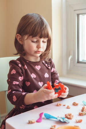 Portrait of cute white Caucasian preschooler girl playing plasticine  indoors at home. Early creativity brain development concept. Children activity. Fine motor skills.