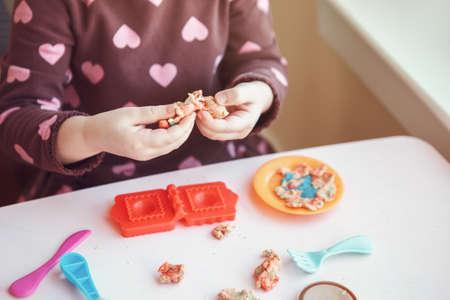 Closeup of child girl hads fingers. Kid playing plasticine  indoors at home. Early creativity brain development concept. Children activity. Fine motor skills. Stock Photo