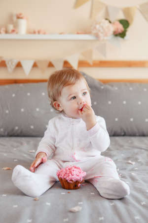 Portrait of cute adorable Caucasian blonde baby girl in white onesie celebrating her first birthday eating pink cupcake. Home indoors cake smash first year concept