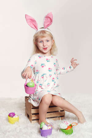 Cute adorable Caucasian child girl wearing Easter bunny rabbit ears sitting on wooden box in studio. Kid holding holiday basket with colorful eggs celebrating traditional  Christian holiday  Stock Photo