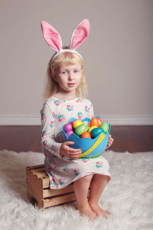 Cute adorable Caucasian child girl wearing Easter bunny rabbit ears sitting on wooden box in studio. Kid holding holiday basket with colorful eggs celebrating traditional  Christian holiday  Stockfoto