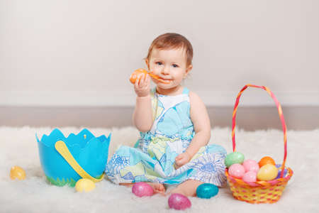 Cute adorable Caucasian baby girl in blue dress sitting on white soft fluffy rug carpet in studio. Kid child playing with Easter colorful eggs celebrating traditional holy Christian holiday.