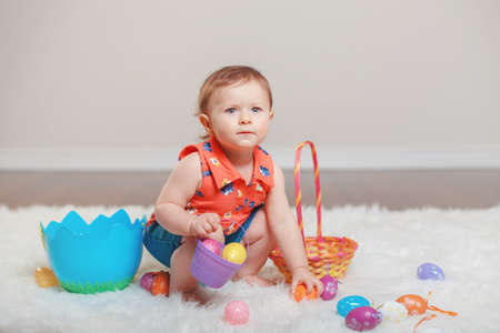 Cute adorable Caucasian baby girl in red shirt and jeans sitting on white soft fluffy rug carpet in studio. Kid child playing with Easter colorful eggs celebrating traditional holy Christian holiday.
