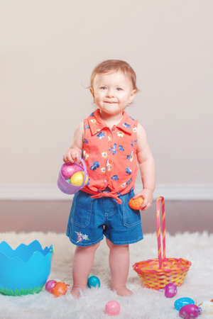 Cute adorable Caucasian baby girl in red shirt and jeans standing on white soft fluffy rug carpet in studio. Kid child playing with Easter colorful eggs celebrating traditional holy Christian holiday.
