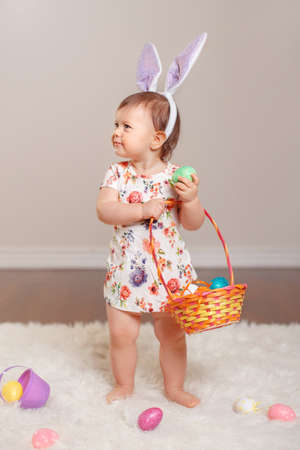 Cute adorable Caucasian baby girl wearing Easter bunny rabbit ears playing in studio indoors. Kid holding basket with eggs celebrating traditional holy Christian holiday Stock Photo