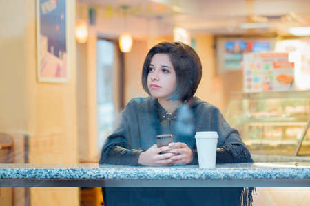 Candid portrait of beautiful young hipster latin hispanic girl woman with short hair bob in grey poncho jacket sitting in cafe  with coffee and cell phone looking away, view through window