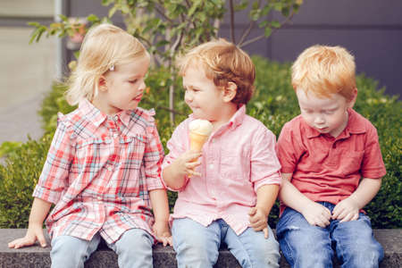 Group portrait of three white Caucasian cute adorable funny children toddlers sitting together sharing ice-cream food. Love friendship jealousy concept. Best friends forever.  Stockfoto