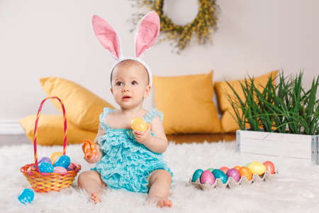 Cute adorable Caucasian baby girl in blue green romper wearing bunny ears sitting in studio. Kid child playing with Easter colorful eggs celebrating traditional holy Christian holiday.