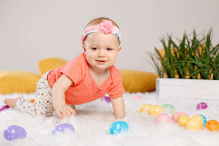 Cute adorable Caucasian baby girl in red onesie t-shirt sitting on white soft fluffy rug carpet in studio. Kid child playing with Easter colorful eggs celebrating traditional holy Christian holiday.