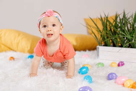 Cute adorable Caucasian baby girl in red t-shirt sitting on white soft fluffy rug carpet in studio. Kid child playing with Easter colorful eggs celebrating traditional holy Christian holiday.