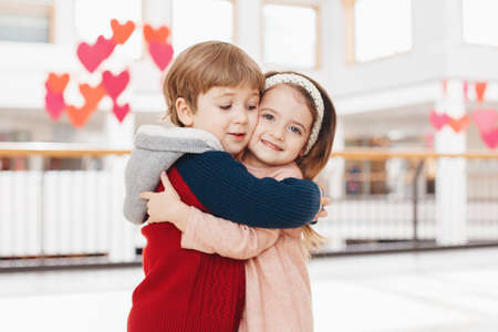 Group portrait of two white Caucasian cute adorable funny children boy and girl hugging kissing each other. Love friendship fun concept. Best friends forever. Imagens