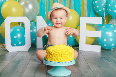 Portrait of cute adorable Caucasian baby boy wearing jeans pants and hat celebrating his first birthday. Cake smash concept. Child kid sitting on floor in studio eating tasty yellow dessert Archivio Fotografico - 101789979