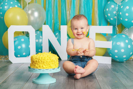 Portrait of cute adorable Caucasian baby boy in jeans pants celebrating his first birthday. Cake smash concept. Child kid sitting on floor in studio eating tasty yellow dessert