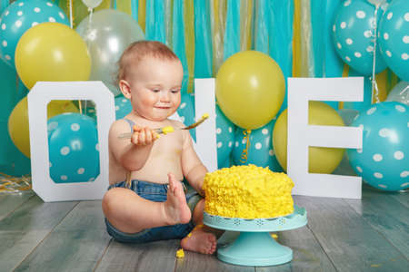 Portrait of cute adorable Caucasian baby boy in jeans pants celebrating his first birthday. Cake smash concept. Child kid sitting on floor in studio eating tasty yellow dessert with spoon